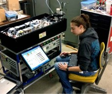 Erin working in the lab with one of NOAA's aircraft-certified, air quality research instruments.